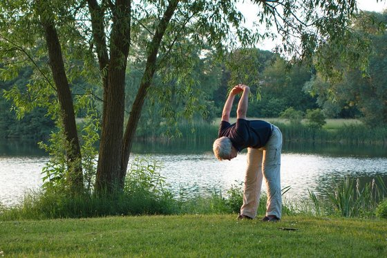 A senior person doing yoga near a lake.
